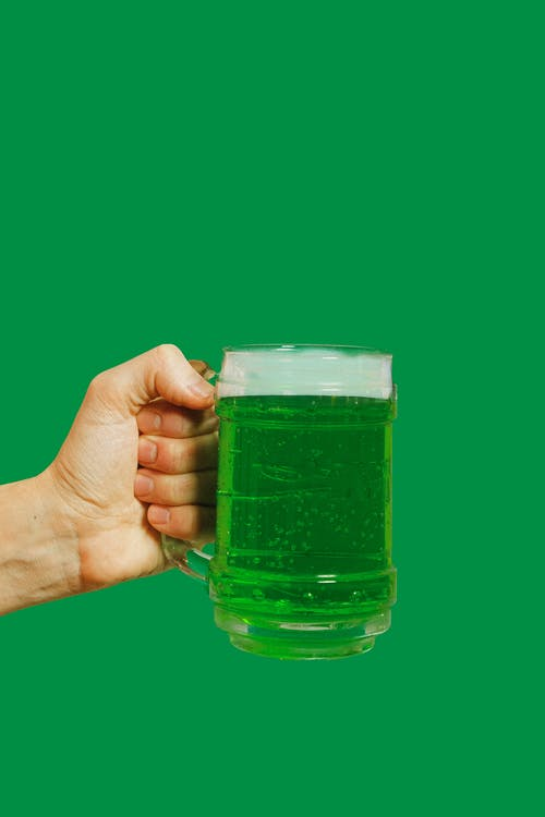 Person Holding Clear Glass Mug With Green Liquid