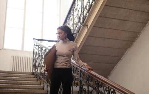 Woman in Gray Turtleneck and Black Pants Standing on Wooden Staircase