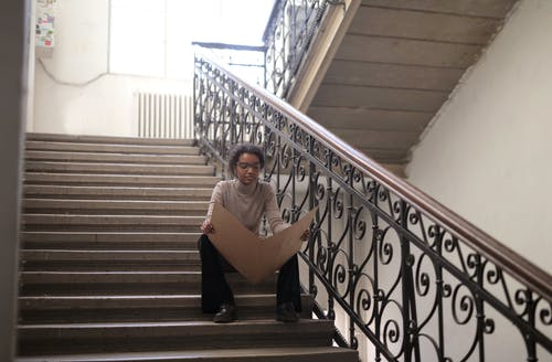 Woman In Long Sleeve Shirt Sitting On Staircase