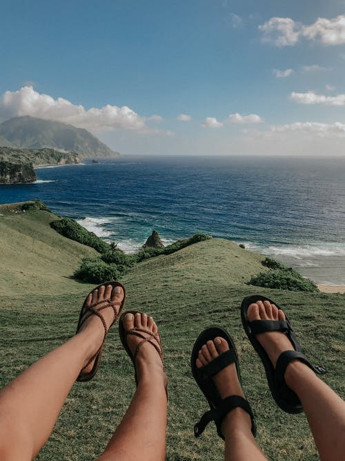 Person Wearing Black Hiking Sandals on Green Grass Field Near Body of Water