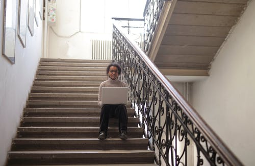 Woman In Long Sleeve Shirt And Black Pants Sitting On Stairs