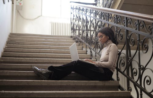 Woman Sitting On Staircase While Using Her Laptop