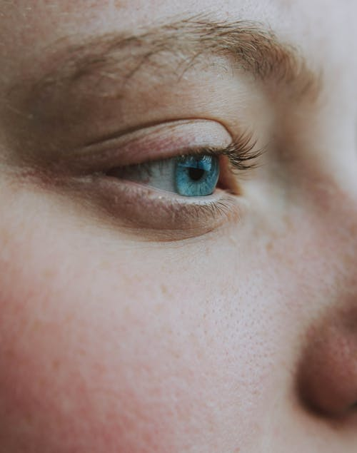 Crop unrecognizable dreamy woman with blue eye