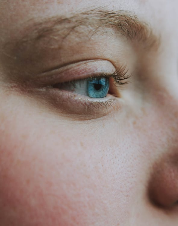 Closeup side view of crop anonymous wistful female looking away with turquoise eye and black eyelashes with brown eyebrows and pores on face skin