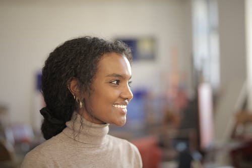 Side view of young smiling African American female in casual outfit standing in modern workshop and looking away on sunny day