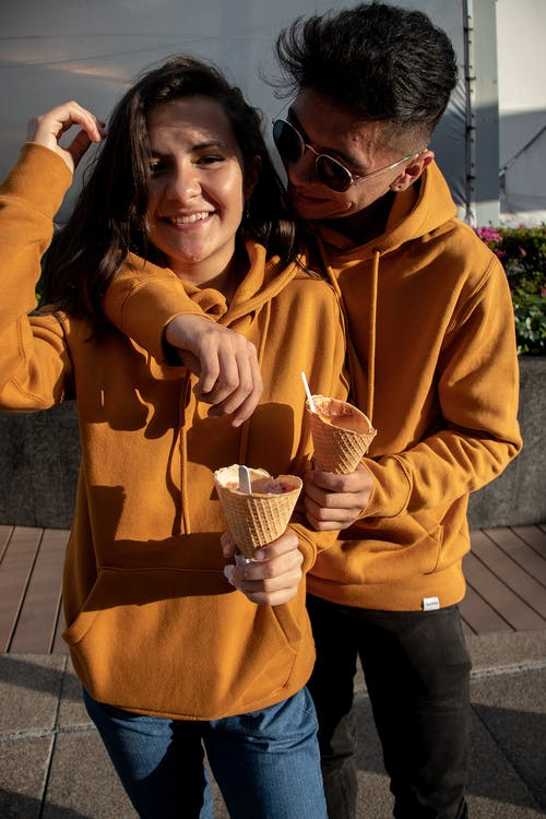 Man And Woman In Orange Hoodie Holding Ice Cream Cone
