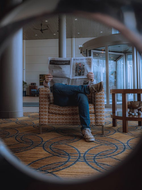 Man Sitting On Brown Sofa Chair Reading The Newspaper