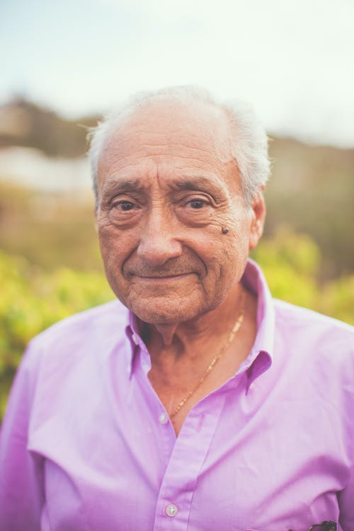 Elderly Man In Purple Button Up Shirt Wearing Gold Necklace