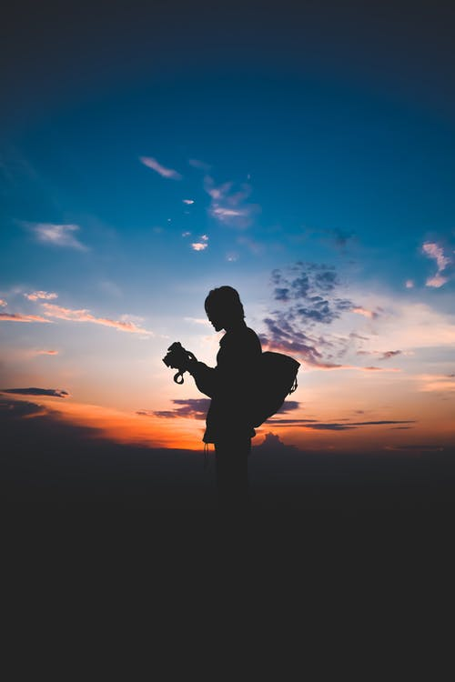 Silhouette of unrecognizable traveler with photo camera at bright sunset