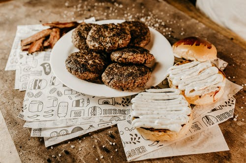 From above of bacon near plate with roasted appetizing patties for burgers and yummy golden bun on ornamental paper sheets on wooden table with sesame seeds
