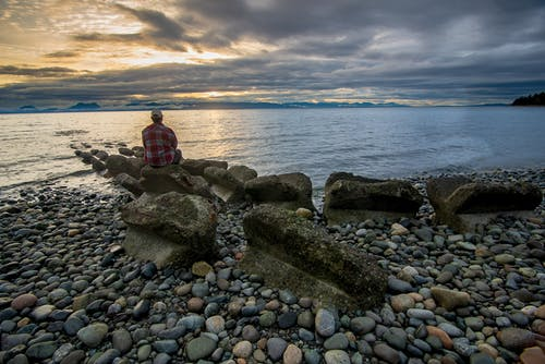 Man Sitting On A Big Rock