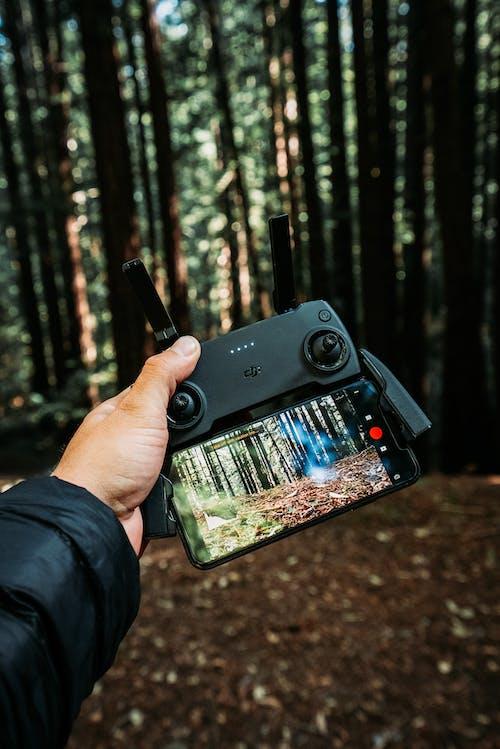 Ernte Anonymen Mann, Der Uav Controller Mit Smartphone Bildschirm Mit Wald Zeigt