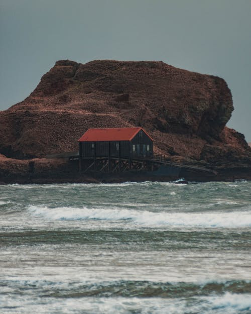 Brown Wooden House on Brown Rock Formation Beside Sea