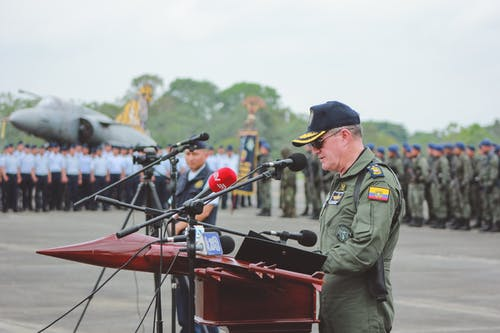 Colonel in uniform giving speech into microphone during national holiday