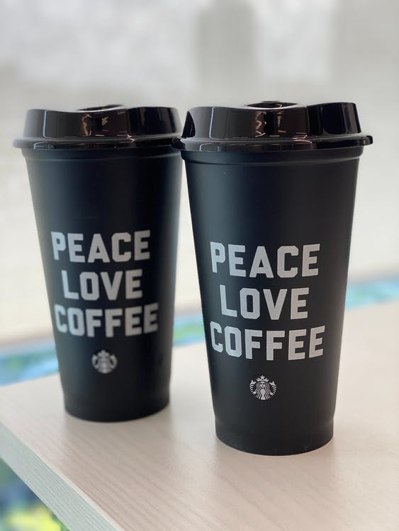 Similar black takeaway plastic glasses with PEACE LOVE COFFEE inscriptions and shiny lids on wooden table for breakfast in morning