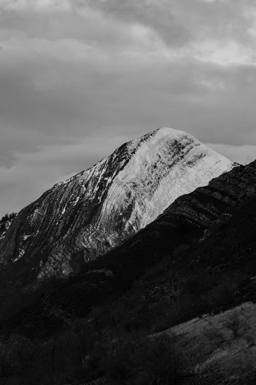 Black and white of high uneven mountain with bristly surface and rounded peak in overcast weather under sky with clouds
