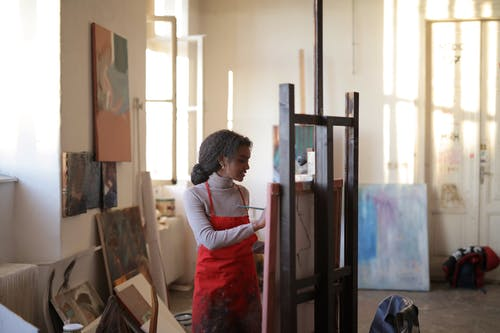 African American woman painting on easel