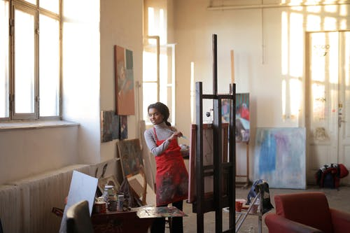 Creative female painting on easel in workshop