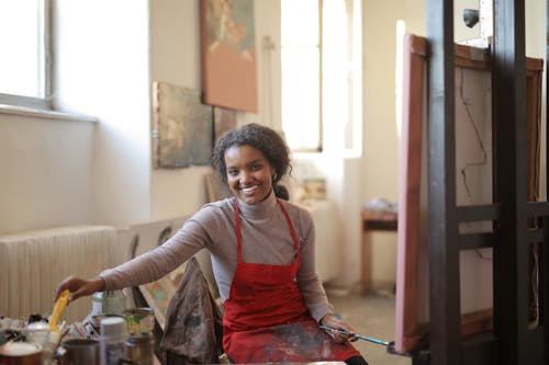 Cheerful smiling African American female in apron sitting on chair in front of easel near table with various tools for painting in creative workshop