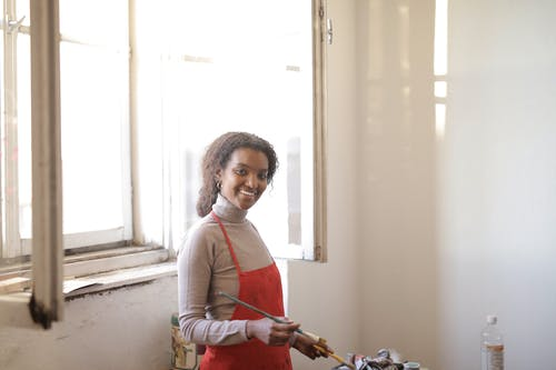 Cheerful black female with paintbrush in studio
