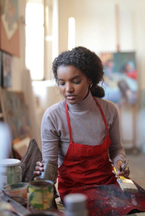 Concentrated ethnic female artist wearing casual clothes and apron standing near table and preparing paints while working with picture in modern studio
