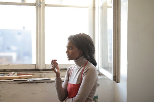 Cheerful woman looking away while standing near window