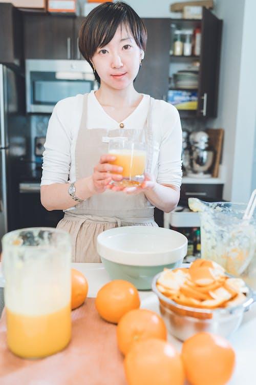 拿著透明的水杯,用黃色液體的白色長袖襯衫的女人
