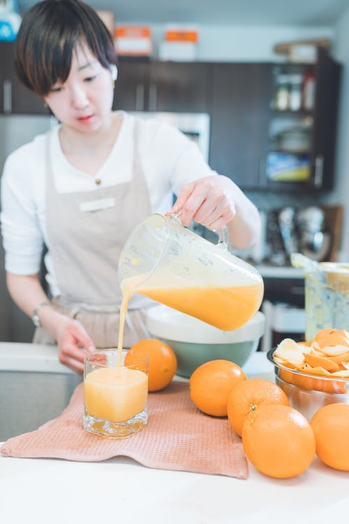 A Woman Pouring Orange Juice in the Glass