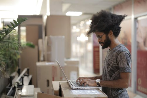 Side view of ethnic male with Afro hairstyle and in casual clothes with eyeglasses using laptop and thinking while working on project in modern workspace