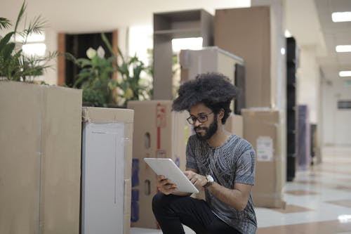 Concentrated young black male employee wearing casual clothes and eyeglasses sitting near boxes and browsing tablet while working in modern workspace