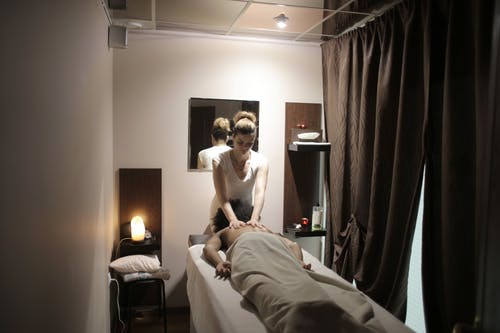 Professional masseuse doing massage for client in salon