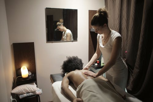 Professional masseuse doing massage of back of client in salon