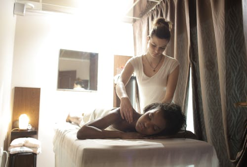 Woman Lying Down In Bed For A Massage