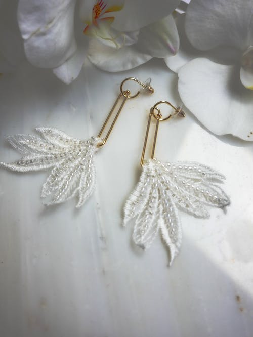 Gold and Silver Earrings on White Textile