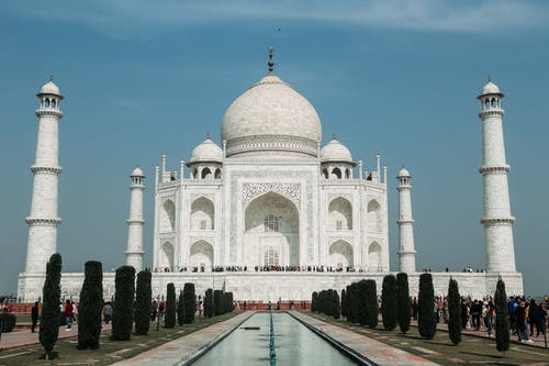 From below of famous facade of Taj Mahal cathedral and national mausoleum of India with decoration on stone walls near pond and trees under serene sky