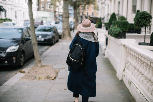 Back view of unrecognizable stylish female tourist with backpack in trendy coat and hat walking along pavement near parked cars on street and modern buildings during daytime