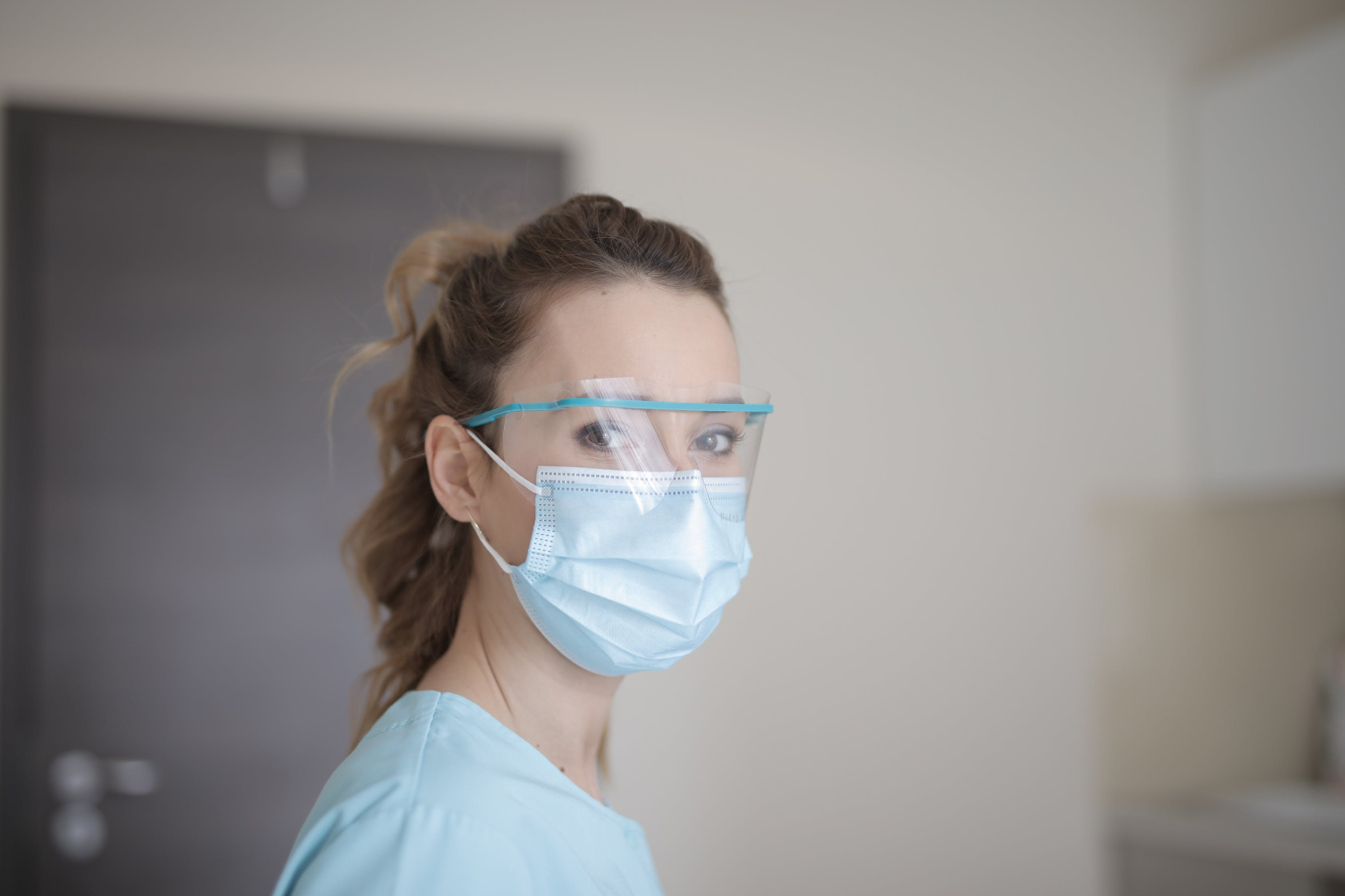A nurse with curly hair wearing a facemask and a face shield looks at the camera