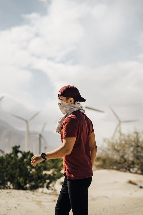 Unrecognizable man with scarf on face walking in sandy terrain terrain near windmills