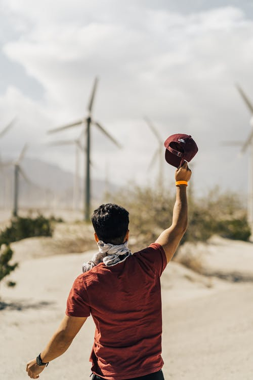Unrecognizable young man with raised arm against windmills farm