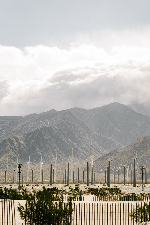 Wind turbines in mountainous valley against cloudy sky
