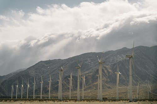 Wind Turbines Near Mountains Under A Cloudy Sky