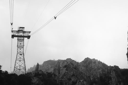 Grayscale Photo Of Power Lines Over The Mountains