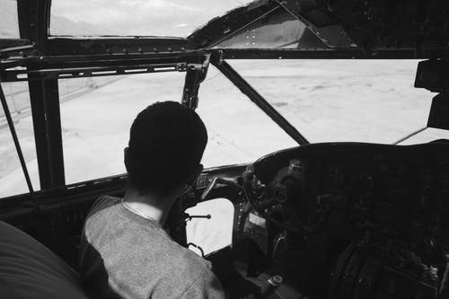 Unrecognizable person sitting in pilot cabin during flight