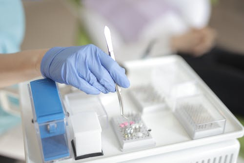 Anonymous medical specialist in latex gloves using forceps to take detail from plastic container while working in modern clinic