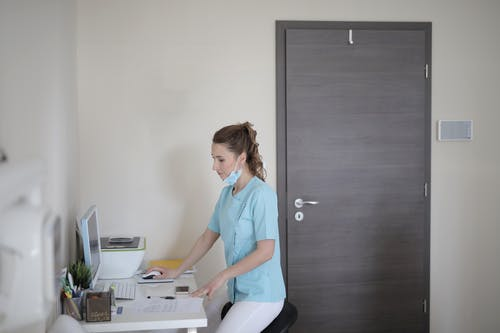 Side view of serious young female doctor in medical mask and uniform standing near table and working on computer while preparing for treatment at modern clinic