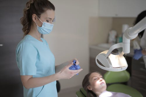 Young female dentist taking off latex gloves after treatment in clinic