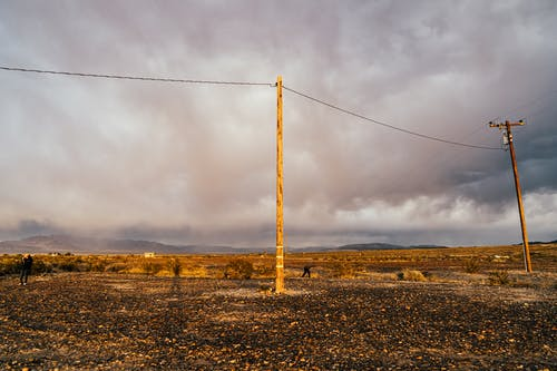 Utility poles near empty rural terrain