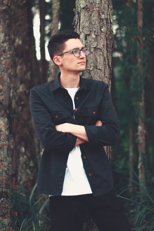 Man In Black Button Up Jacket Standing Beside Tree