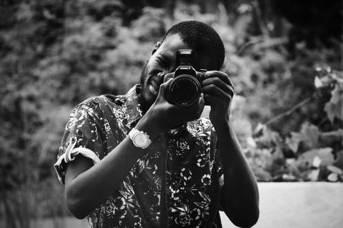 Grayscale Photo of Man Taking Photo Using Dslr Camera