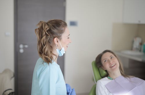 Cheerful young female dentist talking with patient in modern clinic